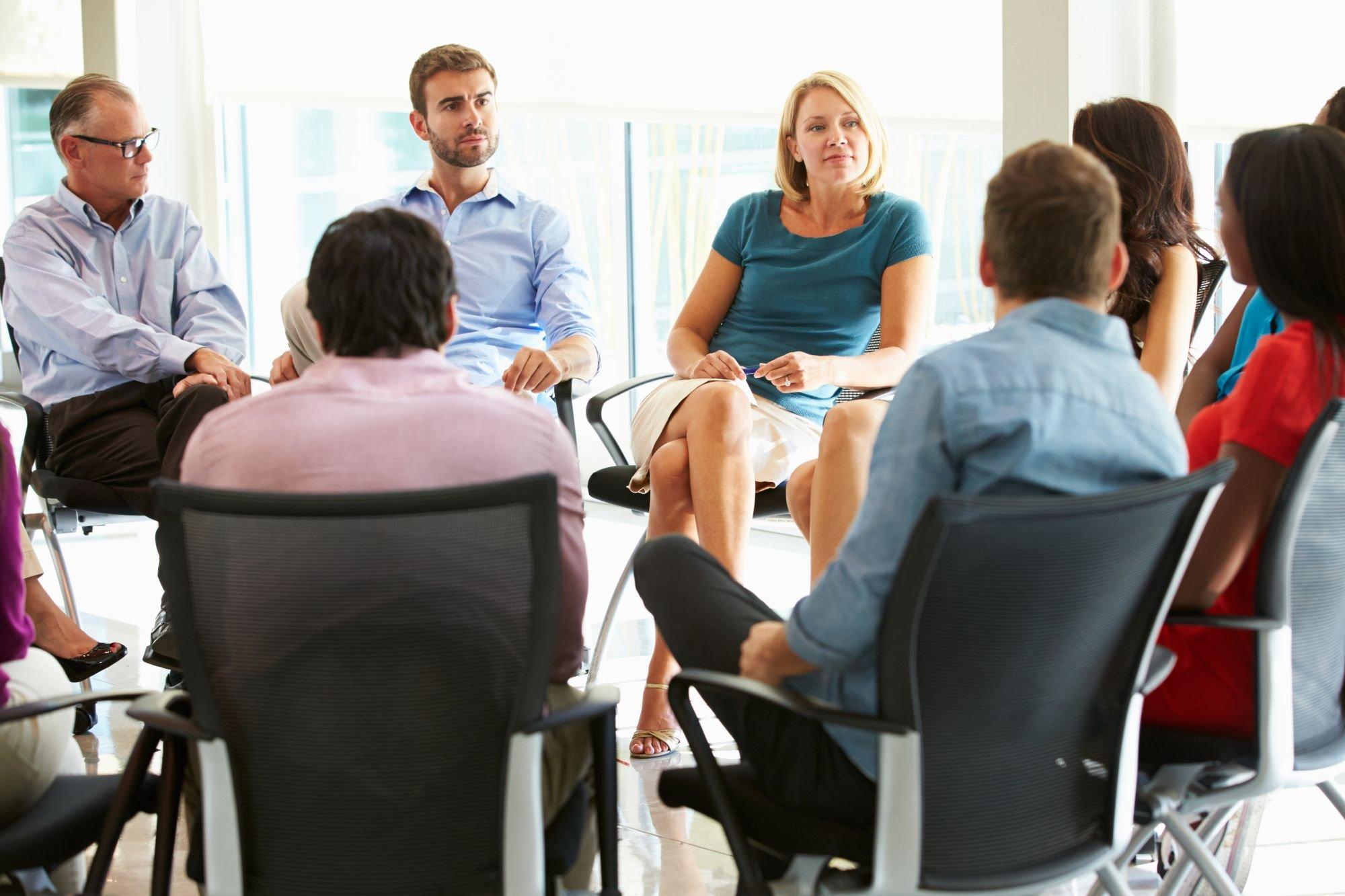 een groep mensen zit in een kring en hoort elkaar aan