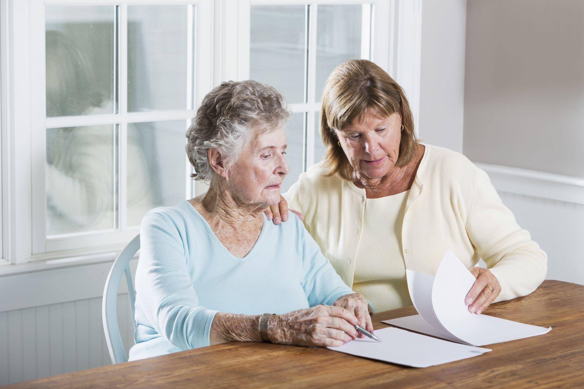 vrouw helpt oudere vrouw met papierwerk