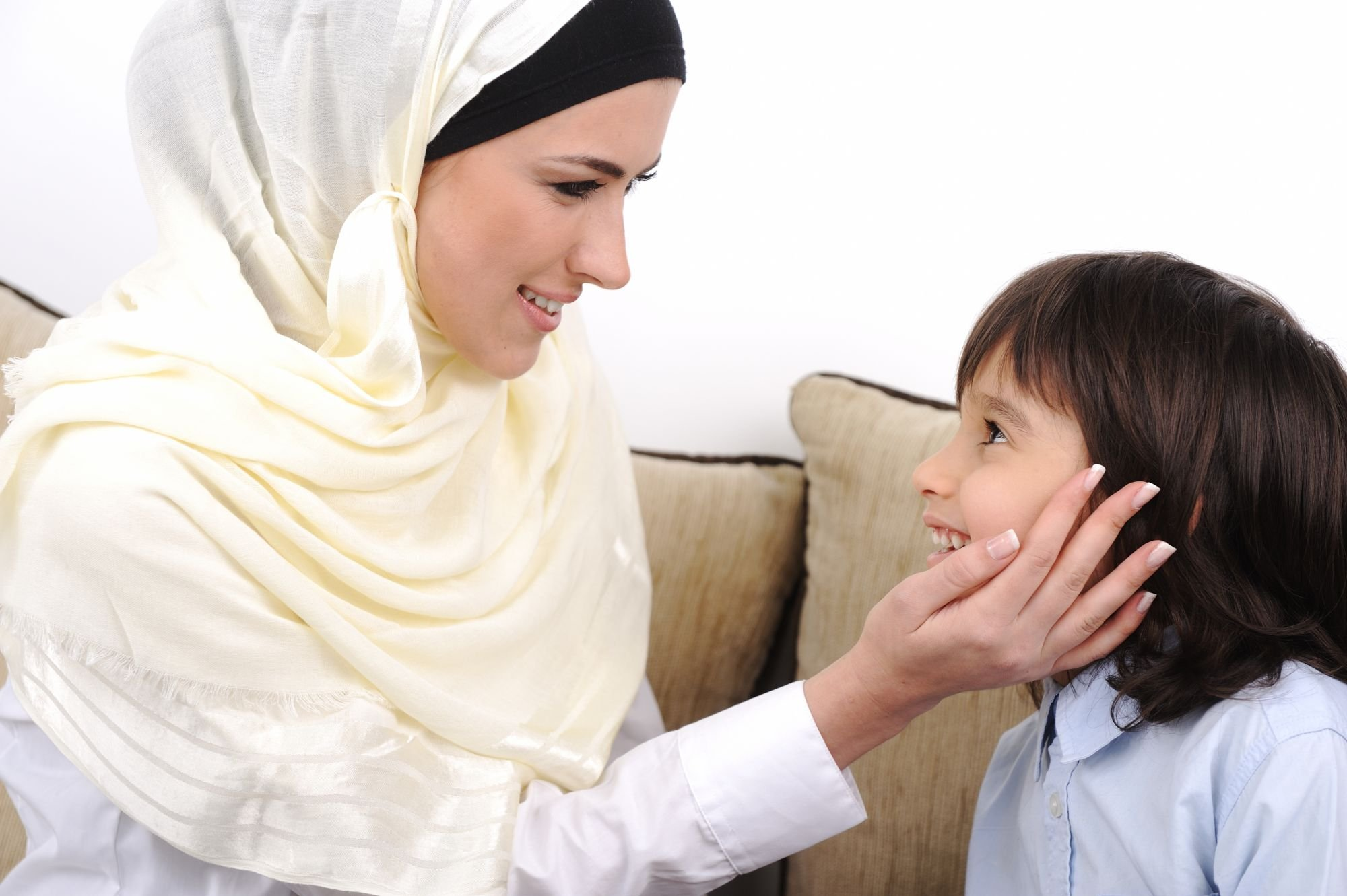 Een vrouw legt haar hand liefdevol op de wang van een kind