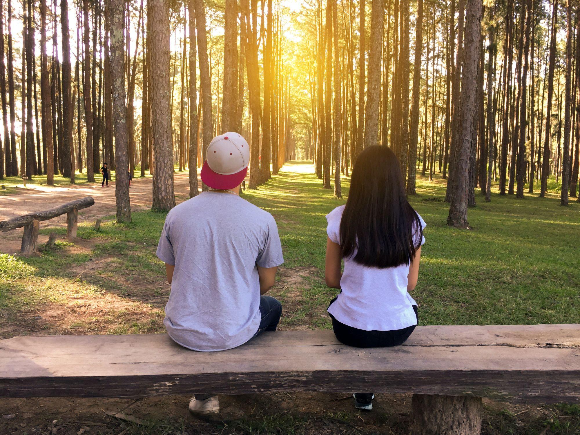 Een man en een vrouw zitten op een houten bankje in het bos. Ze zitten met hun rug gekeerd naar de camera en kijken naar de zonsondergang in de verte.
