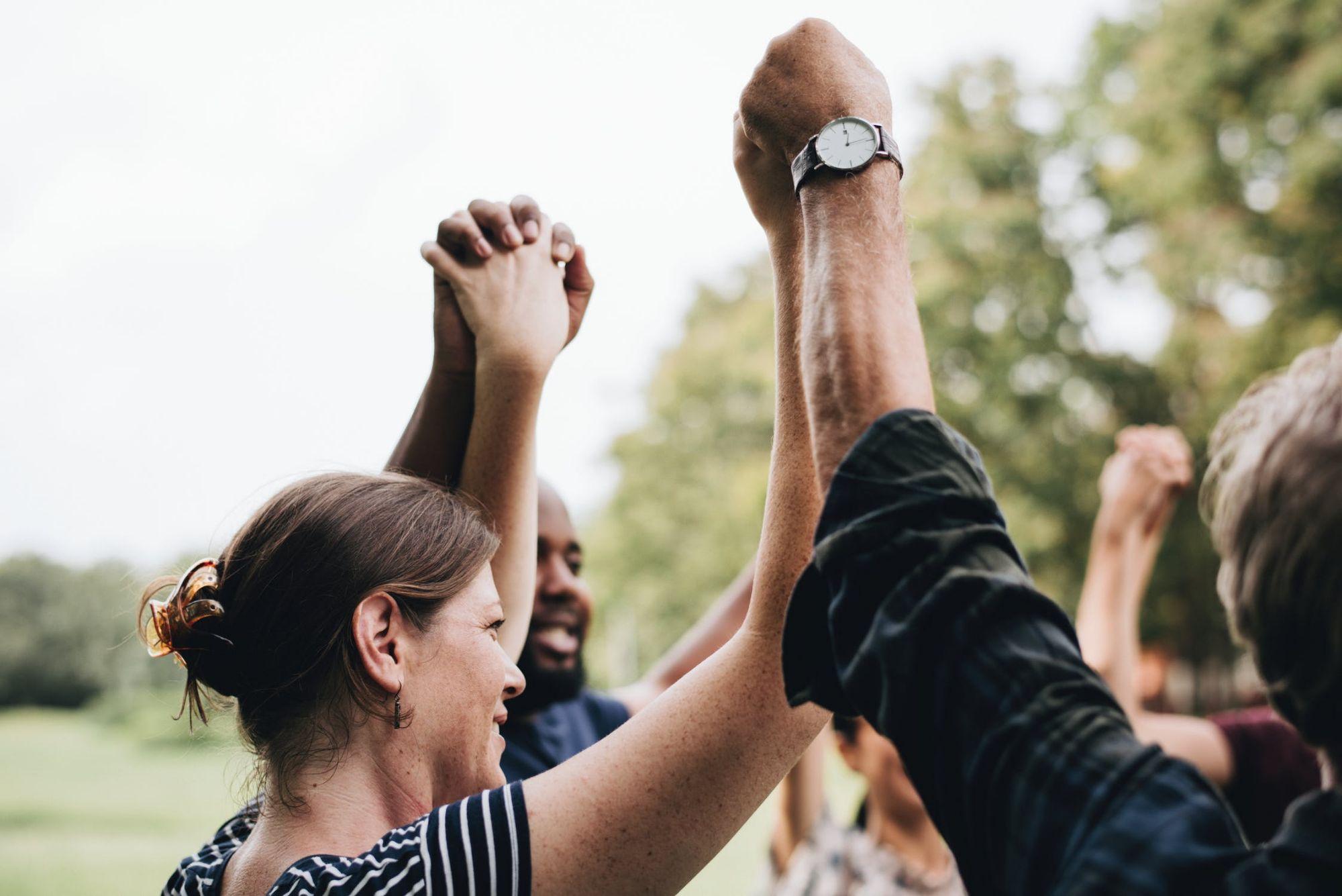 Een groep mensen houden elkaars handen vast en steken deze gezamenlijk op boven hun hoofden