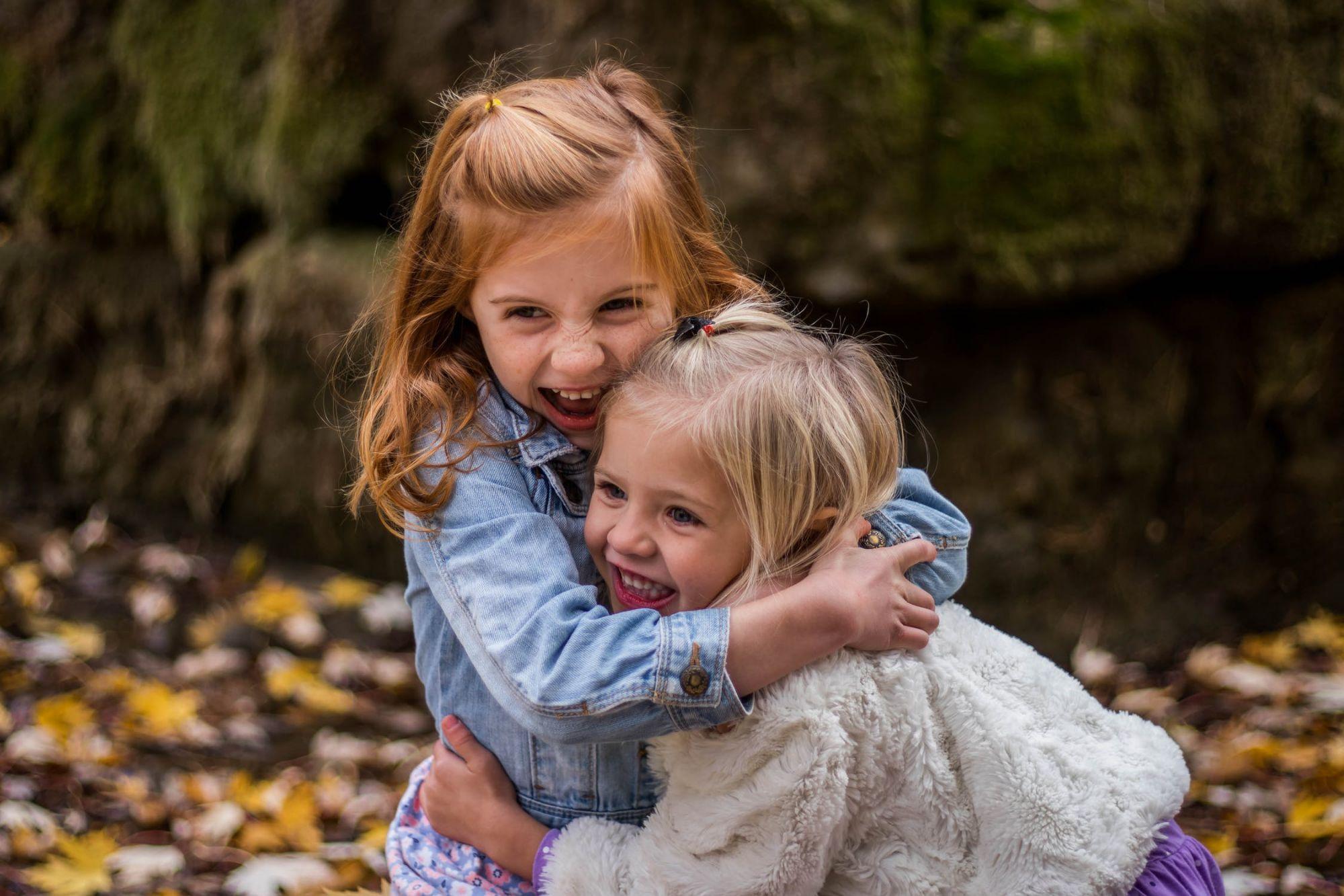 Twee meisjes omhelzen elkaar lachend