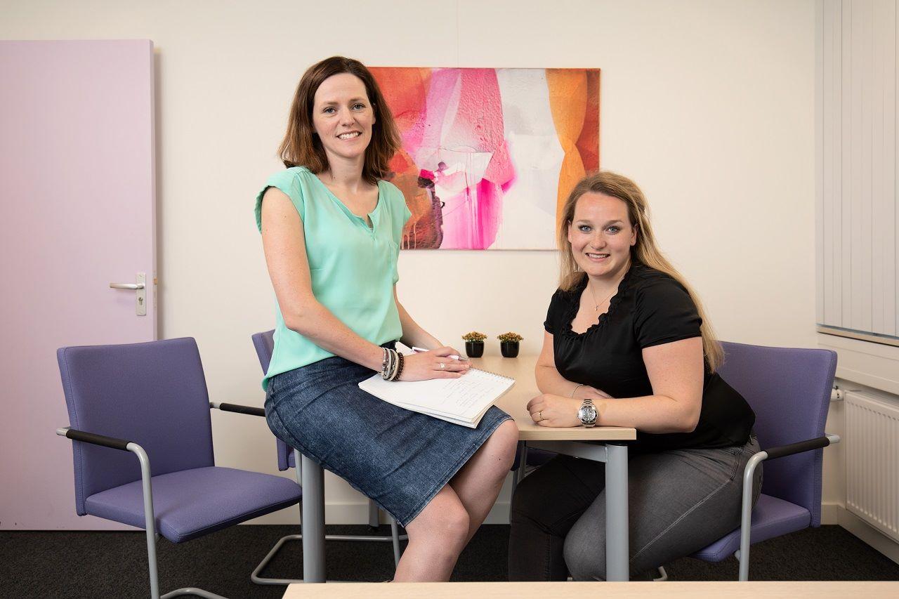 Portretfoto van Caroline Heinemans en Nienke Franken in een kantoor. Caroline zit op het bureau, Nienke zit aan het bureau. Beiden kijken lachend in de camera.