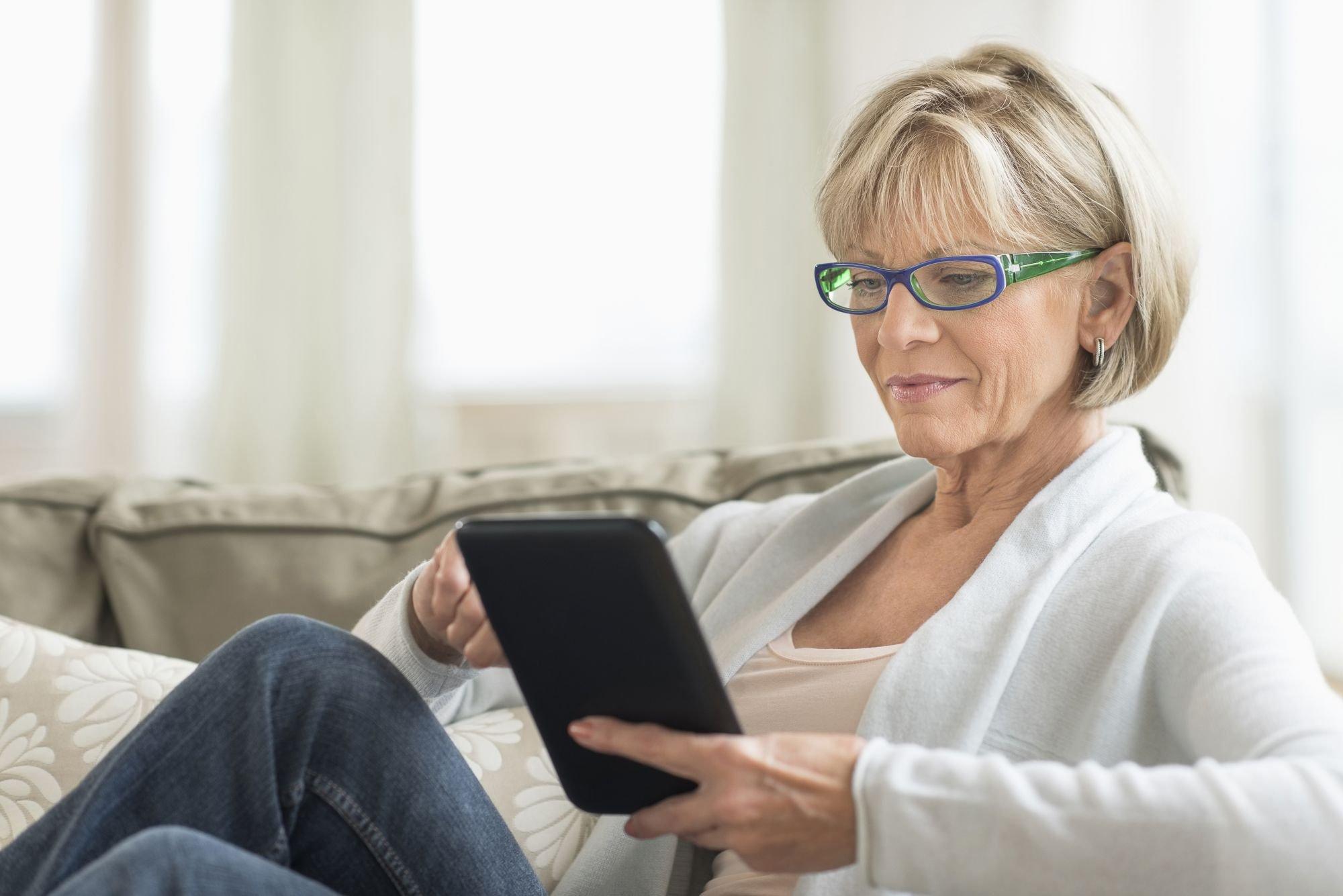 vrouw op een bankstel kijkt op een tablet