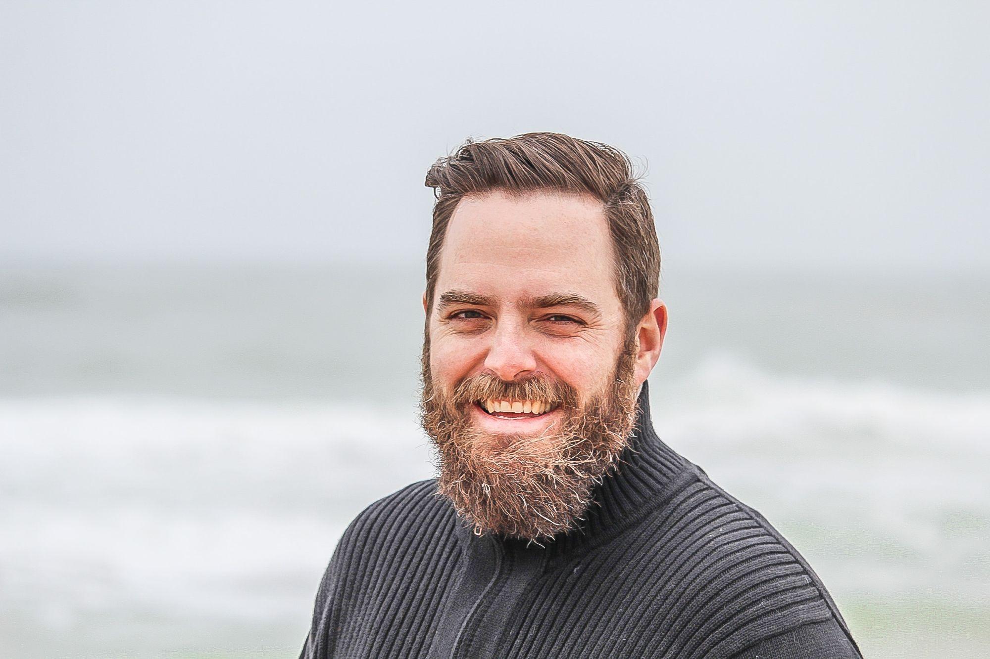 Close-up van man met baard die op het strand staat.