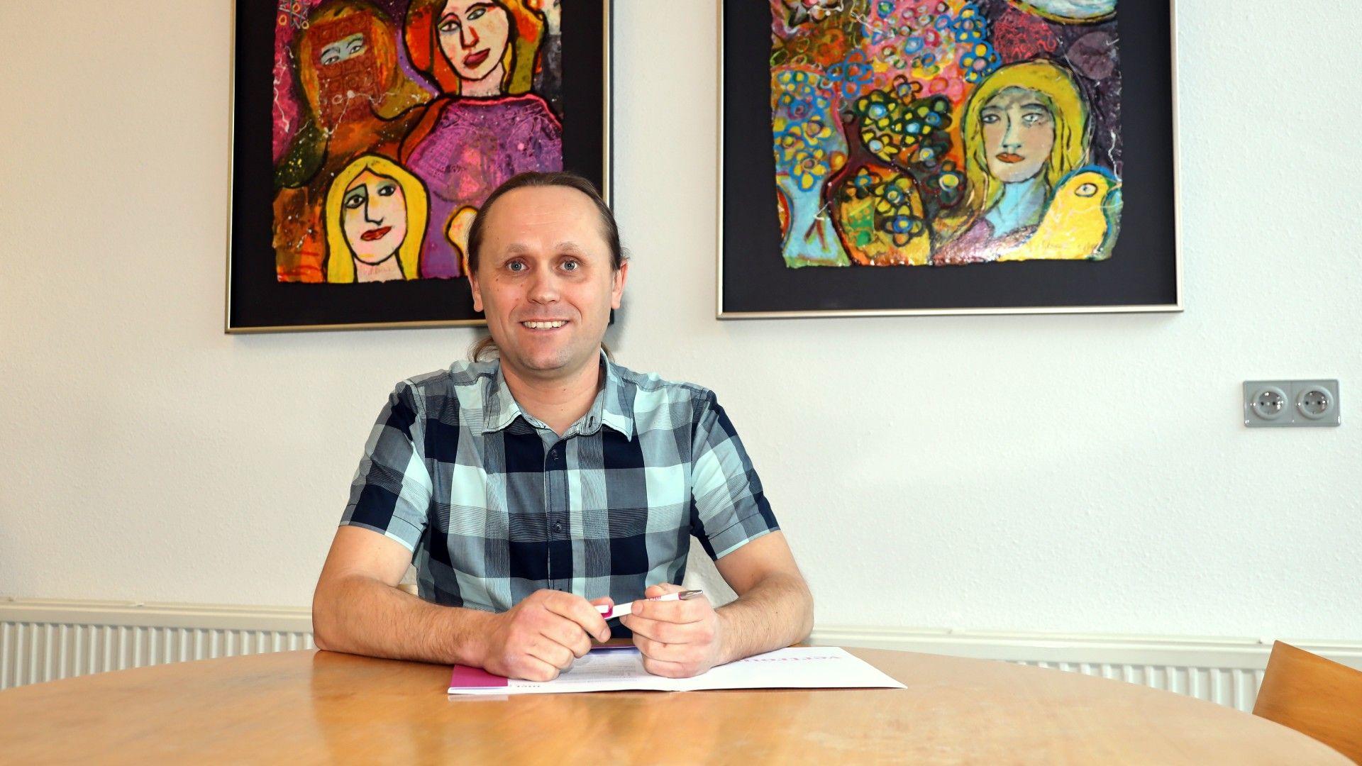 Portretfoto van rehabilitatiewerker Rudy Nordhausen. Hij kijkt lachend achter z'n bureau de camera in, houdt een pen vast en rust met z'n armen op enkele documenten die op het bureau liggen.