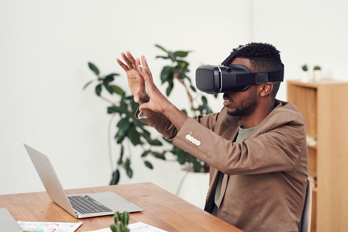 Een man zit achter een bureau en draagt een virtual reality-bril.