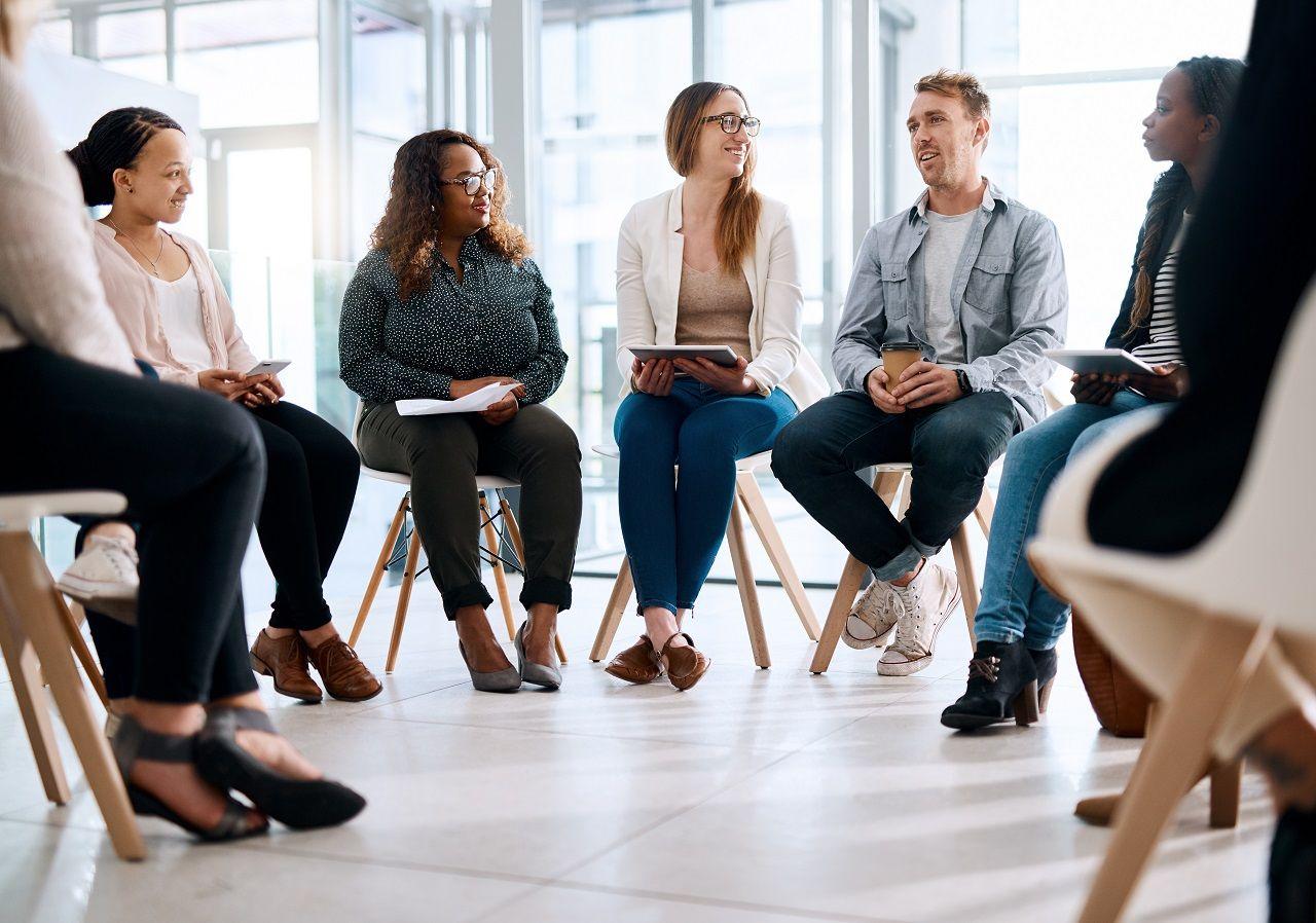 Een groep mensen zitten op stoelen in een kring. Een van de mensen is een man, die iets aan het vertellen is. De groep luistert aandachtig.
