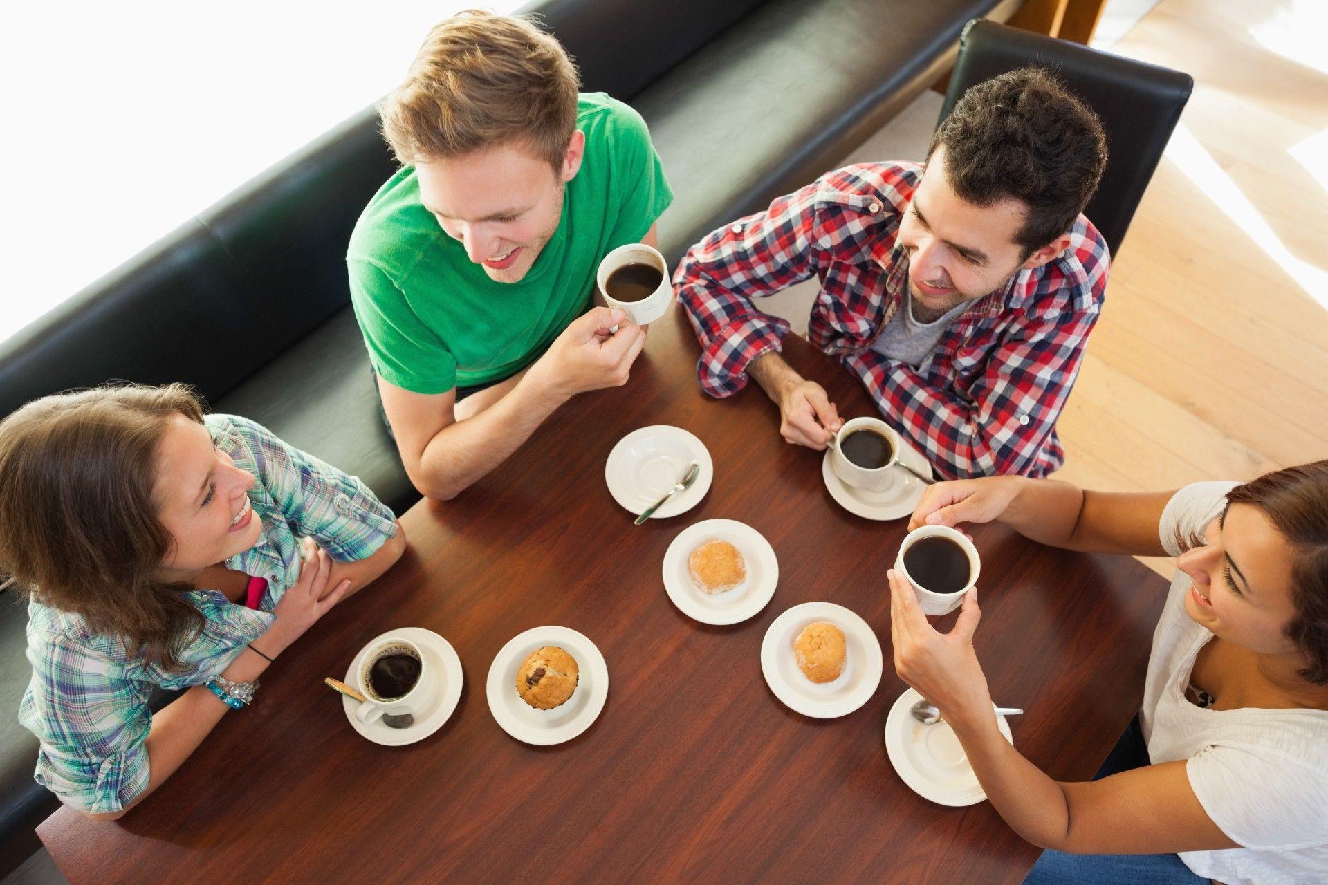 twee vrouwen en twee mannen zitten gezellig aan een tafel koffie te drinken. Er staan ook gebakjes op tafel.