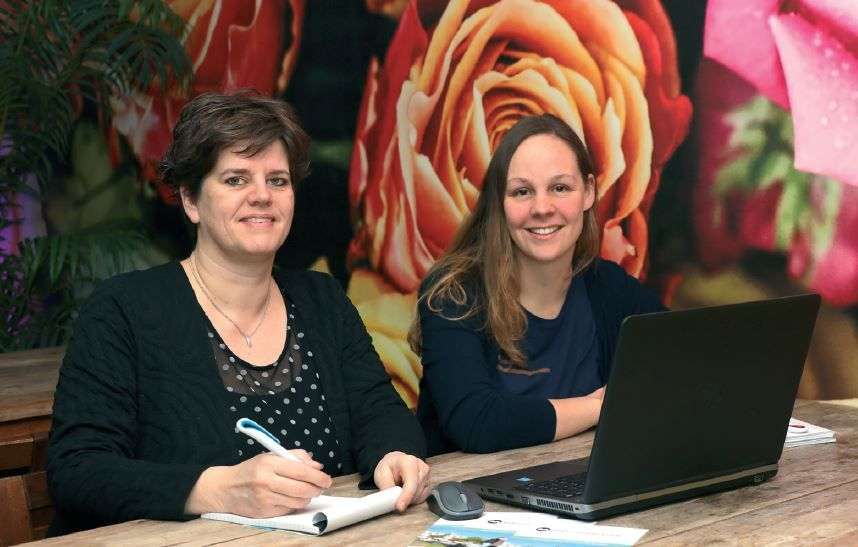Portretfoto van Kim Deenen en Maaike van der Laak tijdens hun werkzaamheden. Ze zitten achter een tafel met een laptop en een notitieblok en kijken in de camera.