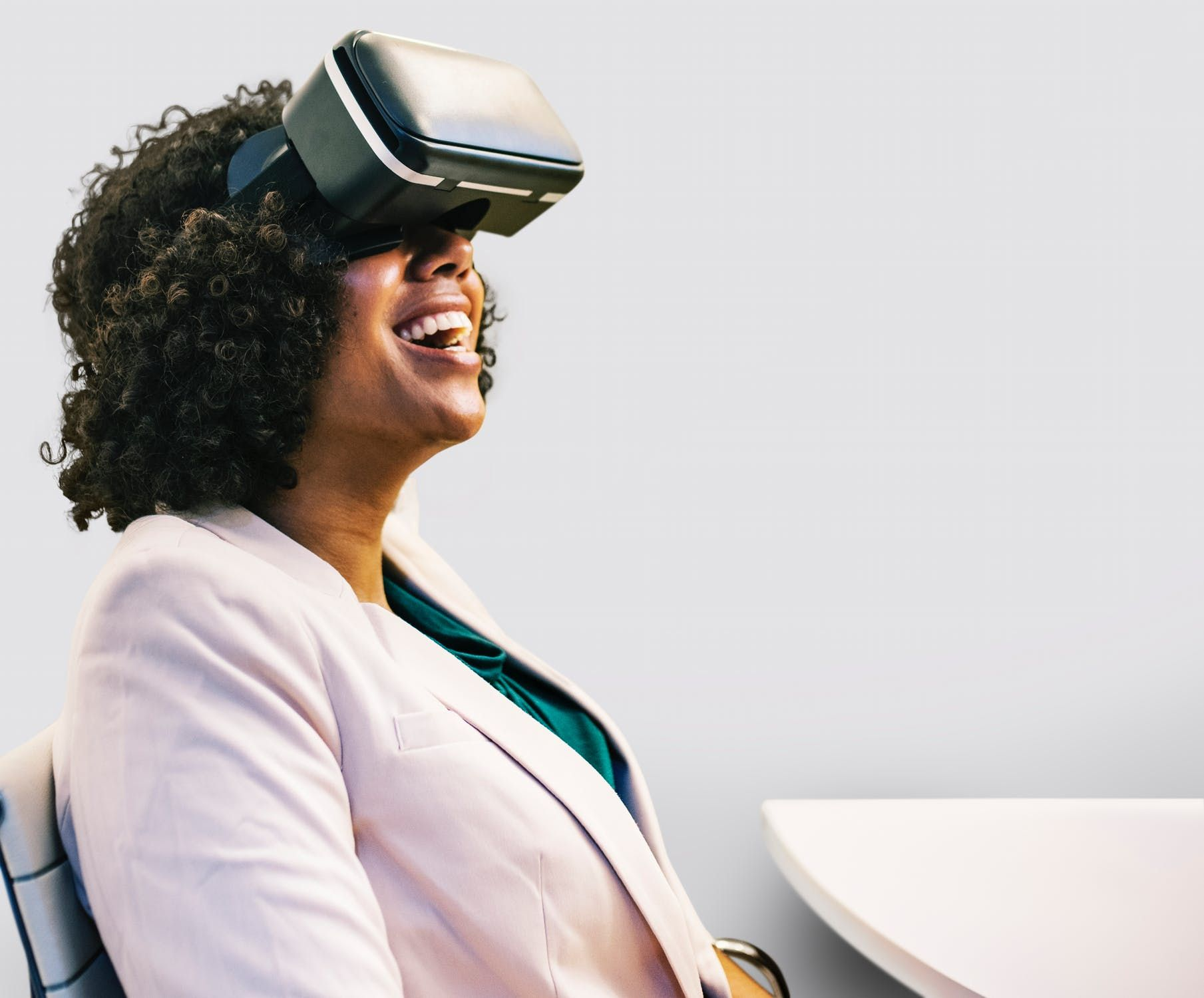 Een mevrouw zit aan een tafel met een Virtual Reality-bril op. Ze kijkt naar boven en lacht voluit.