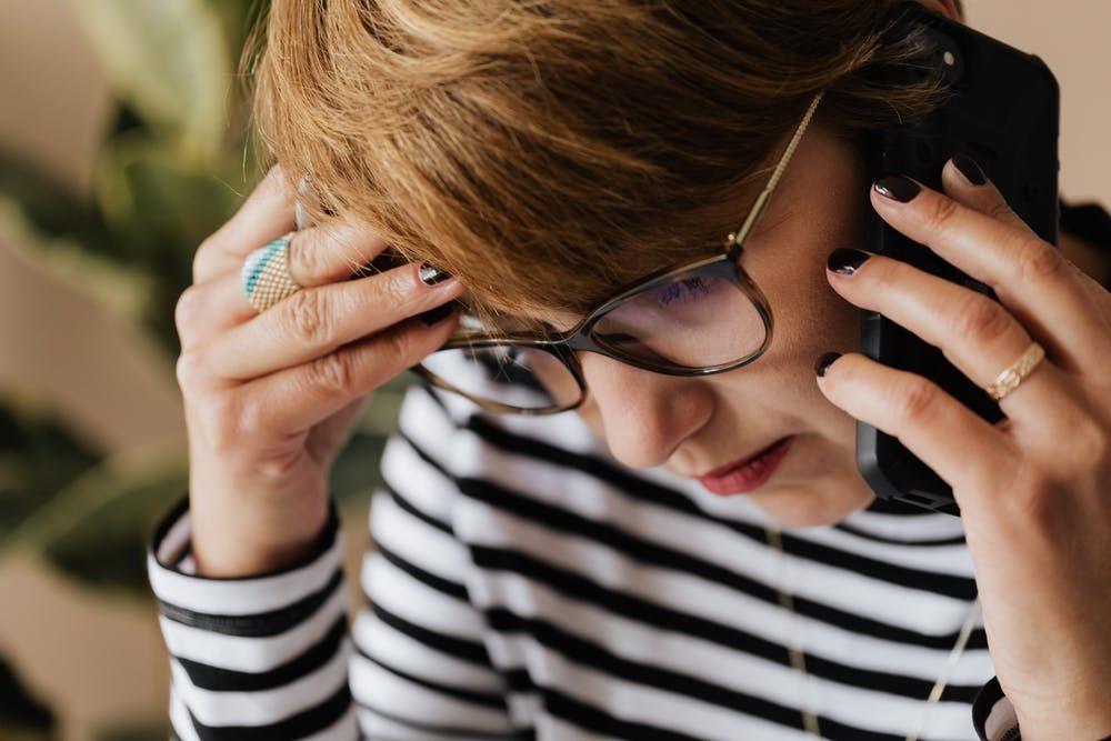 Een vrouw telefoneert met een bezorgde blik