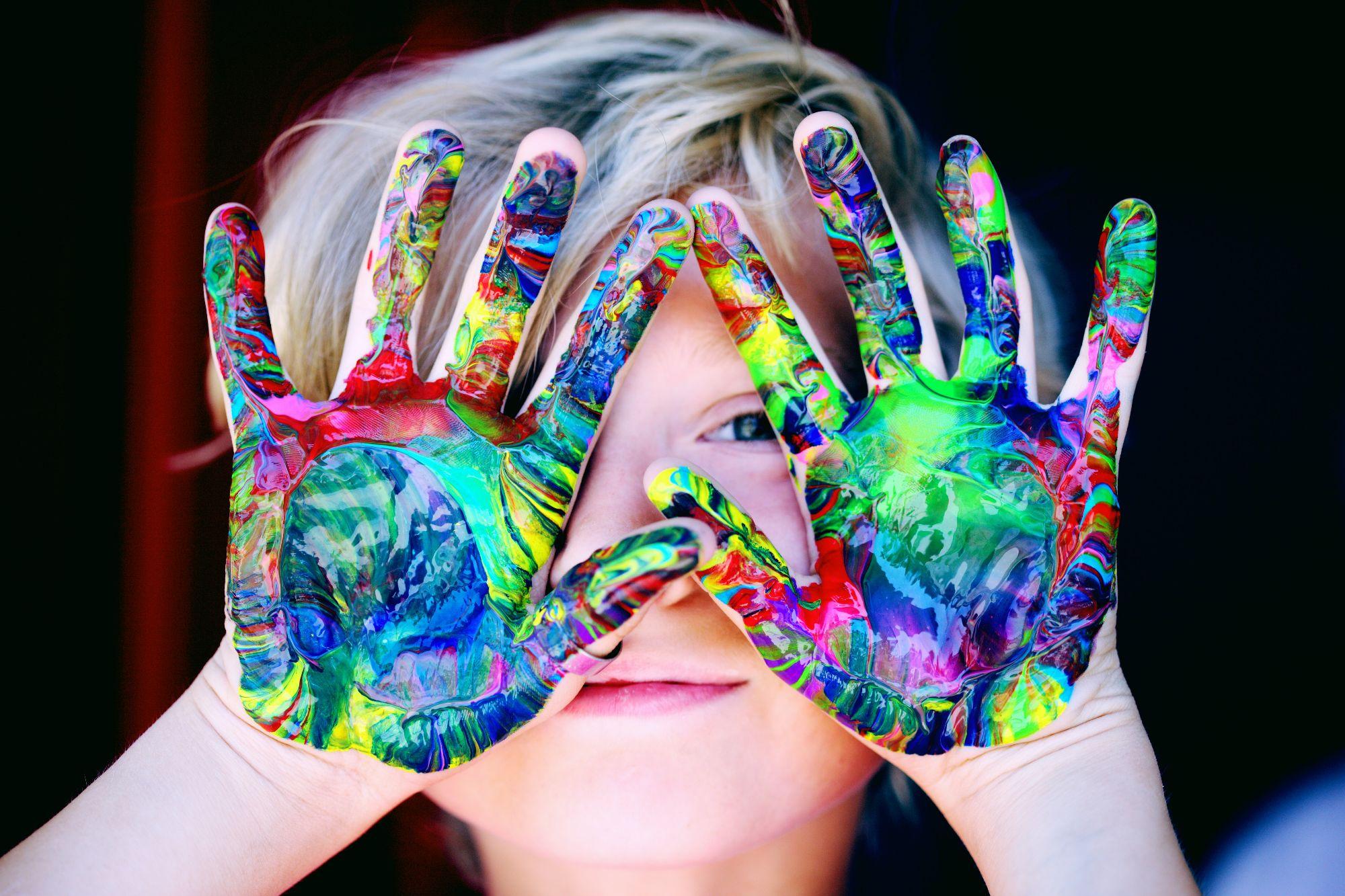 Een jongetje toont zijn met verf bekladde handen